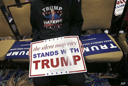 Pablo Ramos, of Orlando, holds a campaign sign as he waits for Republican presidential candidate Donald Trump to speak prior to a campaign event in Tampa, Fla., March 14, 2016.