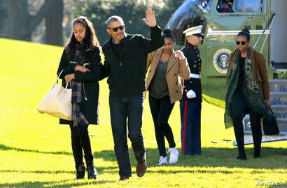 U.S. President Barack Obama waves as he walks with first lady Michelle Obama (R) and their daughters Malia (L) and Sasha on the South Lawn of the White House in Washington January 3, 2016. The Obama family returned from Hawaii, the president's home s...