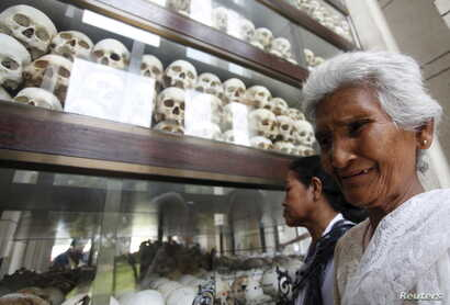 """A woman cries in front of the skulls and bones of more than 8,000 victims of the Khmer Rouge regime during a Buddhist ceremony at Choeung Ek, a """"Killing Fields"""" site located on the outskirts of Phnom Penh, Cambodia, April 17, 2015."""