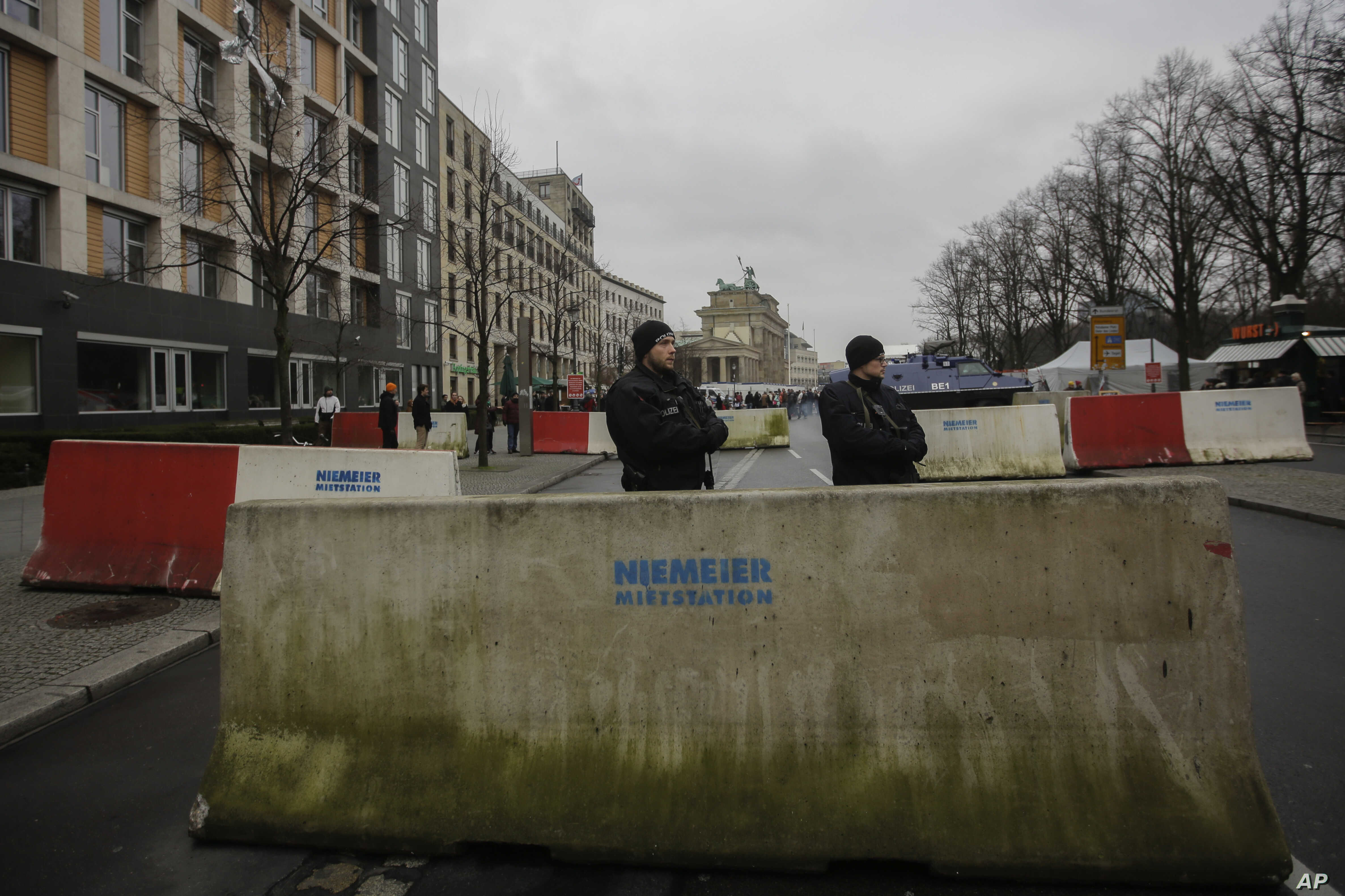 Armed police officers stand behind concrete blocks for protection near the Brandenburg Gate in Berlin, Friday, Dec. 23, 2016.
