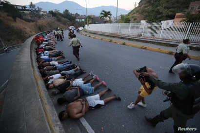 People detained by security forces lie on the street after looting broke out during an ongoing blackout in Caracas, Venezuela, March, 10, 2019.