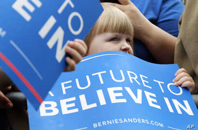 FILE - A young audience member watches Democratic presidential candidate, Sen. Bernie Sanders, I-Vt., speak during a rally in Springfield, Oregon, April 28, 2016.