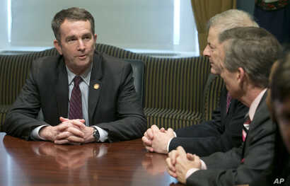 Virginia Gov. Ralph Northam, left, address State Senators and Delegates as they gather to inform him that they are ready to adjourn the 2018 session of the Virginia General Assembly at the Capitol in Richmond, Va., March 10, 2018.