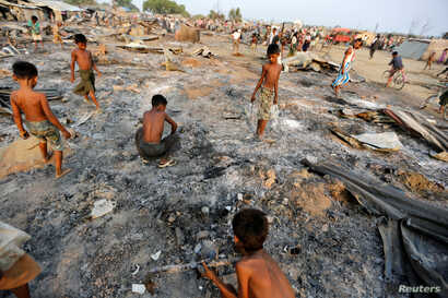 FILE -  Boys search for useful items among the ashes of burnt houses after fire destroyed shelters at a camp for internally displaced Rohingya Muslims in the western Rakhine State near Sittwe, Myanmar, May 3, 2016.