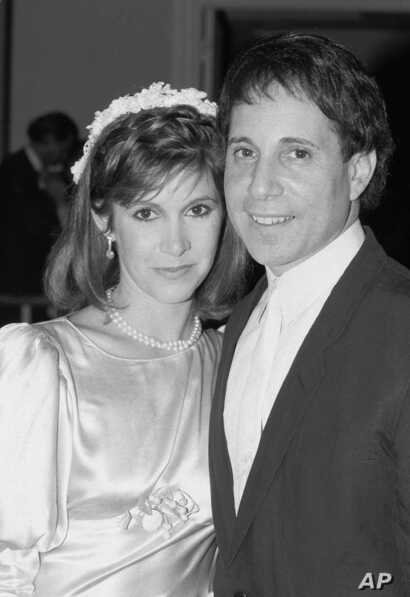 FILE - Actress Carrie Fisher and singer Paul Simon pose in doorway of midtown New York City apartment where their wedding reception was in progress, Aug. 16, 1983.