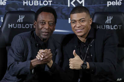 Brazilian soccer legend Pele, left, and French soccer player Kylian Mbappe pose during a photo call in Paris, April 2, 2019.