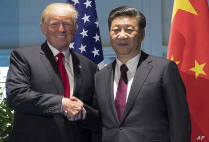 President Donald Trump and Chinese President Xi Jinping shake hands as they arrive for a meeting on the sidelines of the G-20 Summit in Hamburg, Germany, July 8, 2017.