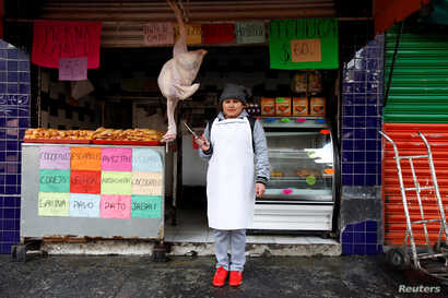 Cristina Alvarez, 29, a butcher, poses for a photograph while standing outside her and her husband's butcher shop, in Mexico City, Mexico, Feb. 25, 2017.