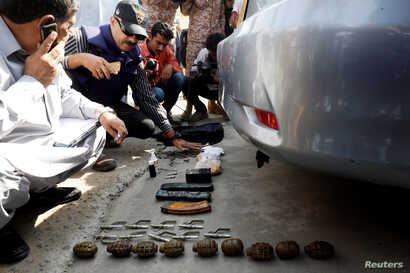 Members of the bomb disposal unit, checking the explosives recovered from a bag, after an attack on the Chinese consulate, in Karachi, Pakistan, Nov. 23, 2018.
