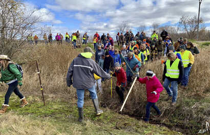 FILE - In this Oct. 23, 2018, file photo, volunteers cross a creek and barbed wire near Barron, Wis., on their way to a ground search for 13-year-old Jayme Closs who was discovered missing Oct. 15 after her parents were found fatally shot at their ho...