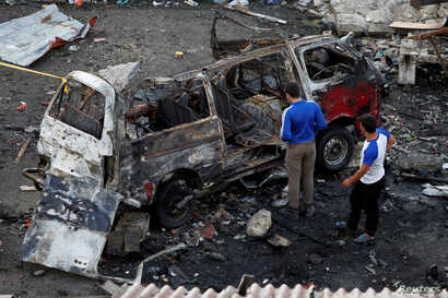 Men inspect a wrecked vehicle after explosions hit a bus station in Jableh, in Syria's Latakia province, May 23, 2016.