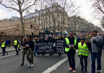 """""""Yellow vest"""" protesters in Paris carry a banner calling for rights for the unemployed. (L. Bryant/VOA)"""