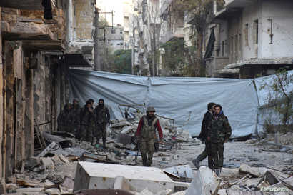 Syrian government soldiers walk amid rubble of damaged buildings after they took control of al-Sakhour neighborhood in Aleppo, in this handout picture provided by SANA, Nov. 28, 2016.