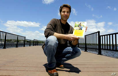 "FILE - David Goldman poses with his book ""A Father's Love"" in Red Bank, N.J., May 5, 2011. Goldman became the poster dad for the issue of international child abductions when his ex-wife ran off with his son, Sean, to Brazil. He finally got custody of..."