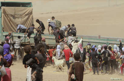 Displaced people from the minority Yazidi sect jump onto a truck as they make their way toward the Syrian border town of Elierbeh of Al-Hasakah Governorate, Aug. 10, 2014.