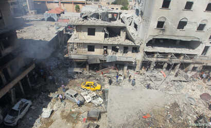 Residents inspect a damaged site after airstrikes on a market in the rebel controlled city of Idlib, Syria, Sept. 10, 2016.