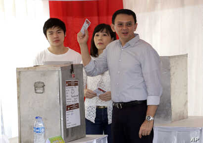 "Jakarta Governor Basuki ""Ahok"" Tjahaja Purnama who is seeking for his second term in office, his wife Veronica and son Nicholas, left, cast their ballot at a polling station during the runoff election in Jakarta, Indonesia, April 19, 2017."