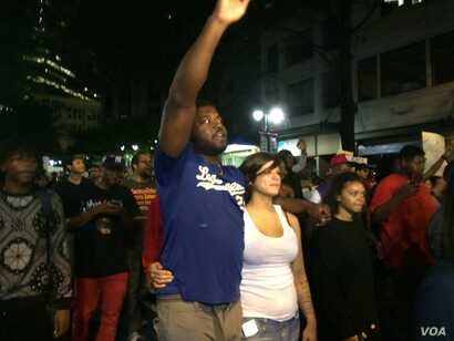 Protestors are out for the fourth night in Charlotte, marching through the uptown area, as helicopters continue to circle above, in Charlotte, North Carolina. Demonstrators are protesting a police shooting that killed an African-American man on Tuesd...
