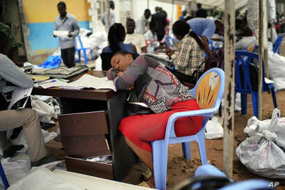 An exhausted Congolese independent electoral commission (CENI) official rests as results are tallied for the presidential election, at a local results compilation center in Kinshasa, Congo, Jan. 6, 2019.