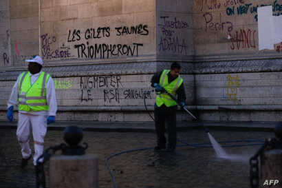 """Workers clean around the Arc de Triomphe a day after a yellow vests (gilets jaunes) demonstration against rising oil prices and living costs, Dec. 2, 2018 in Paris. Graffiti on the monument reads """"yellow vests will triumph."""""""
