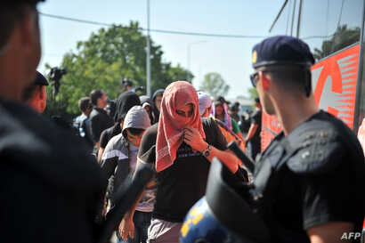 A Croatian policeman stands guard as migrants from Middle Eastern countries board a bus near the Croatia-Serbia border in Tovarnik, on Sept. 17, 2015.