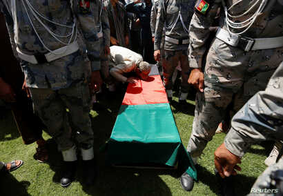 A relative kisses the coffin of an Afghan soldier, who was killed last night during a gun fight between Afghan border forces and Pakistani forces in Torkham, during his funeral in Nangarhar province, Afghanistan, June 14, 2016.