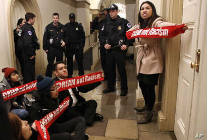 """Diana Colin, right, with the Coalition for Humane Immigrant Rights, shouts, """"McCarthy you have no heart,"""" as the group from California protests outside the office of House Majority Leader Kevin McCarthy, Jan. 18, 2018, on Capitol Hill in Washington, ..."""