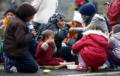 FILE - Migrants rest before crossing the Austrian-German border in Achleiten, Austria, across from Passau, Germany, Oct. 29, 2015.