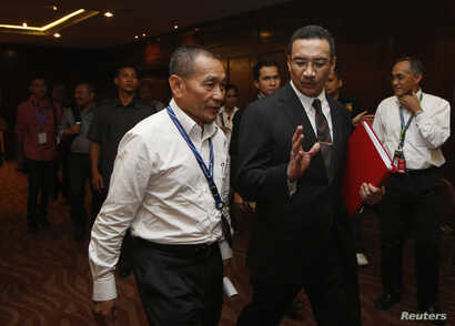 Malaysia's acting Transport Minister Hishamuddin Hussein leaves with Malaysia Airlines Chief Executive Officer Ahmad Jauhari Yahya (L) after a news conference on the search for the missing Malaysia Airlines Flight MH370, March 25, 2014.