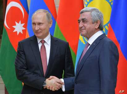 FILE - Russian President Vladimir Putin, left, and then-Armenian President Serzh Sargsyan shake hands ahead of an informal meeting of the CIS (Commonwealth of Independent States) leaders at the Novo-Ogaryovo residence outside in Moscow, Russia, Dec. ...