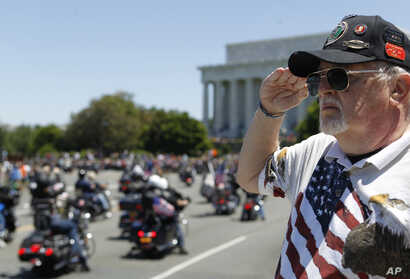 """Ken Caryl of Dale City, Virginia salutes the motorcyclists, many of them are veterans, as they ride across the Memorial Bridge into Washington during the annual Rolling Thunder """"Ride for Freedom,"""" May 26, 2013."""
