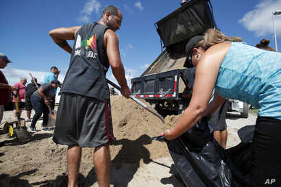 Giovanni Rivera, left, and Nuvia Rivera fill a sandbag, Sept. 12, 2018, in Virginia Beach, Va., as Hurricane Florence moves towards the eastern shore.