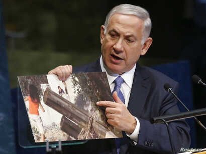 Israel's Prime Minister Benjamin Netanyahu refers to a photograph as he addresses the 69th United Nations General Assembly at the U.N. headquarters in New York, Sept. 29, 2014.