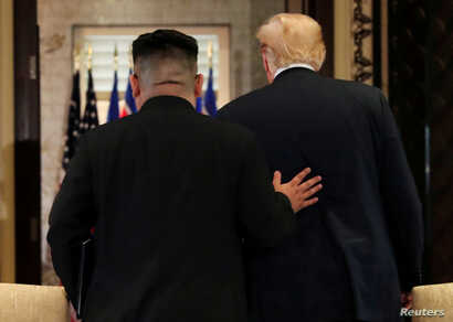 U.S. President Donald Trump and North Korea's leader Kim Jong Un leave after signing documents that acknowledge the progress of the talks and pledge to keep momentum going.