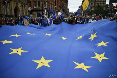 Protestors carry a giant EU flag during an anti-Brexit march on the first day of the Conservative Party annual conference in Manchester on Oct. 1, 2017.