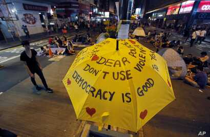 An umbrella, which has become an icon of the protest, reads pro-democracy messages above the student-led protest site in the Mong Kok district of Hong Kong, Monday, Oct. 20, 2014.