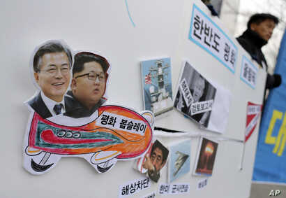 Pictures of South Korean President Moon Jae-in (L) and North Korean leader Kim Jong Un (2nd-L) are seen on a sign during a rally to denounce the United States' policy against North Korea and demand the peaceful Winter Olympics in Seoul, South Korea, ...