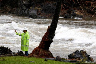 A Hawaii County employee photographs a river swollen by Hurricane Lane in Hilo, Hawaii, Aug. 25, 2018.