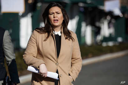 White House press secretary Sarah Huckabee Sanders talks with reporters outside the White House, Dec. 18, 2018.