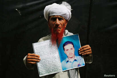 Shodeen Khan 77, holds a photo of his son, Mustaqeem Khan, a former student of the Islamia College Peshawar who has been missing for nine years, is seen at a human rights rally by the Pashtun Tahaffuz Movement (PTM), in Karachi, Pakistan, May 13, 201...