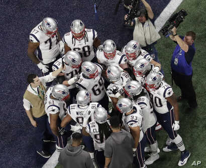 The New England Patriots huddle before the NFL Super Bowl football game between the Los Angeles Rams and the New England Patriots, Feb. 3, 2019, in Atlanta.
