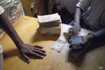 FILE - A Mogadishu money changer checks a U.S. $100 bill with a counterfeit detection device in a market in the city in Mogadishu, Dec. 8, 1992.