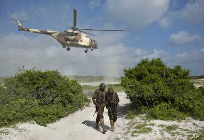 FILE - Two Kenyan army soldiers shield themselves from the downdraft of a Kenyan air force helicopter near the seaside town of Bur Garbo, Somalia, Dec. 14, 2011.