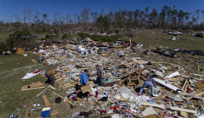 Cindy Sanford, second from right, sifts through the debris with help from her brother, Tim Lancaster, from left; daughter, Kayla Causey; and stepfather, Michael Boutwell, while retrieving personal items after a tornado destroyed Sanford's home in Bea...