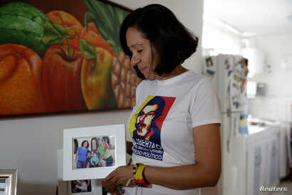 FILE - Elky Arellano, wearing a T-shirt depicting her husband, Marcelo Crovato, holds a photo of them with their children during an interview with Reuters in Caracas, Venezuela, Nov. 17, 2016.