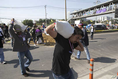 Anti-government protesters carry sand bags to set up road blocks during a rally outside the government complex in Bangkok, Jan. 13, 2014.
