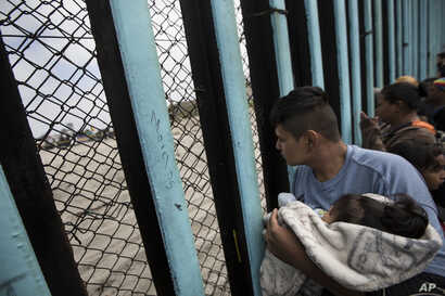 A member of the Central American migrant caravan, holding a child, looks through the border wall toward a group of people gathered on the U.S. side, as he stands on the beach where the border wall ends in the ocean, in Tijuana, Mexico, April 29, 2018...