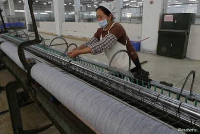 FILE - A worker disentangles wool yarn at a spinning machine at a factory owned by Hong Kong's Novetex Textiles Limited in Zhuhai City, Guangdong Province, China, Dec. 13, 2016.