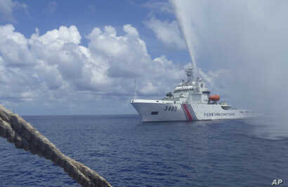 FILE - In this Sept. 23, 2015, file photo, Chinese Coast Guard members approach Filipino fishermen as they confront each other off Scarborough Shoal in the South China Sea, also called the West Philippine Sea.