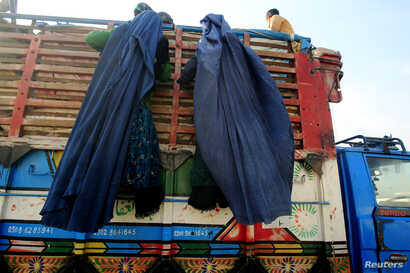 Afghan refugee women, clad in a burqa, climb on a truck to be repatriated to Afghanistan, at the United Nations High Commissioner for Refugees (UNHCR) office on the outskirts of Peshawar February 13, 2015. Afghan immigrants ordered out of Pakistan in...